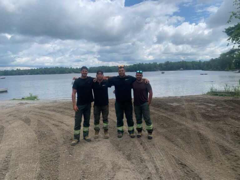 Four tree removal Arborists wearing tree removal uniforms standing on a white sandy pitch near the edge of the water